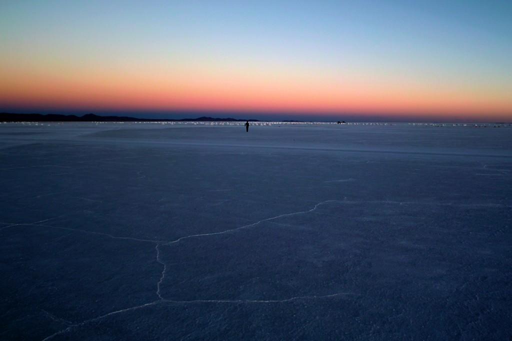 夕暮れのウユニ塩湖を歩く人