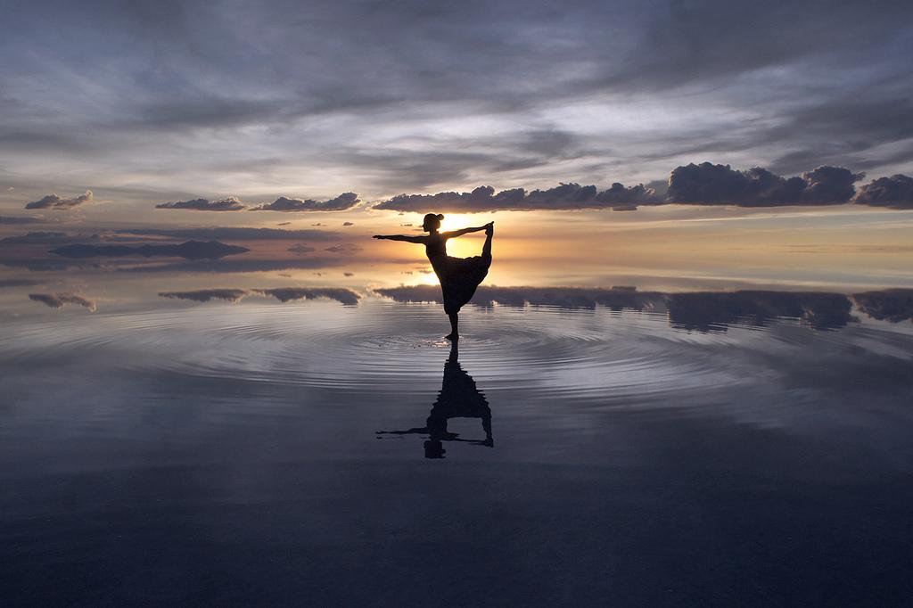 太陽を背景にウユニ塩湖上でポーズをとる女性