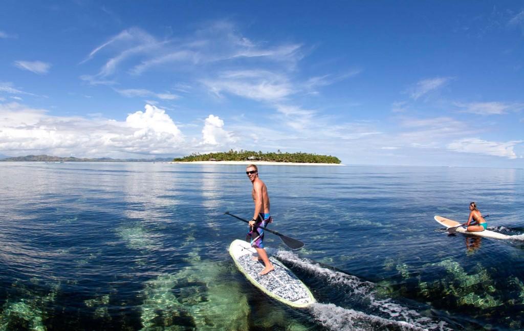 サーフボードでタバルア島へ向かう人々