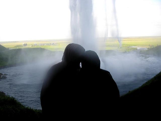 セリャラントスフォスの滝の裏側で寄り添うカップル