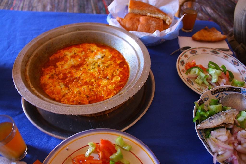 サハラ砂漠の中で食べるモロッコ料理の画像です。